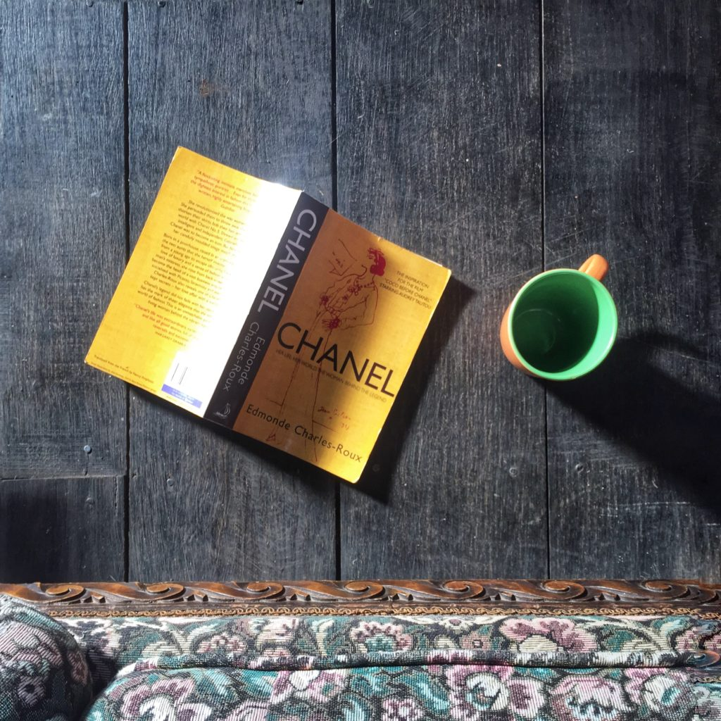 Photo of a Chanel biography book face down on a wooden floor beside an empty cup of coffee.