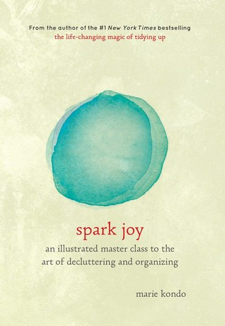 The book cover for 'Spark Joy: an illustrated master class to the art of decluttering and organising' by Marie Kondo, with a beige background and abstract green watercolour circle in the centre, and book title beneath